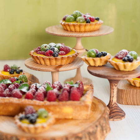 dessert stand: Delicious fruit tart made with raspberries, gooseberries and blueberries on the wooden stand   Shallow DOF