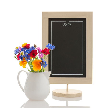 Empty restaurant menu chalkboard with wildflowers in milk jar isolated on white  photo