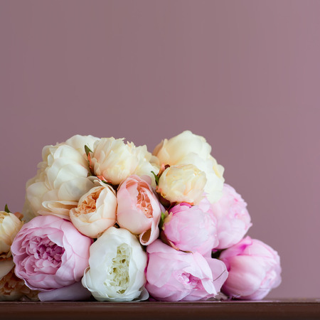 artifical: Bouquet made of artifical pink peony laying on a  wood surface  Shot against pink wall background  Shallow DOF  Stock Photo
