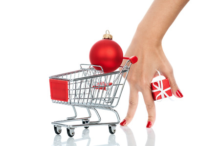 imitating: Woman hand imitating a customer with shopping trolley isolated on white background. Conceptual image - buying christmas presents. Stock Photo