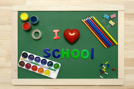 teaching crayons: I love school phrase made with multicolored letters on green chalkboard with stationery.