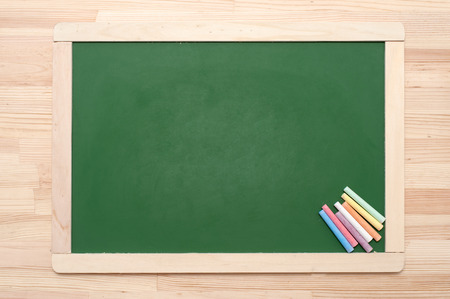 blankness: Closeup of blank green blackboard with pieces of coloured chalks on wooden surface.