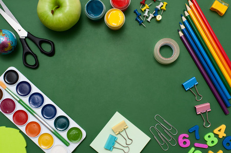 school things: School supplies on blackboard background. Empty space in the middle of green blackboard. Education concept