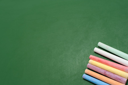 blankness: Closeup of blank green blackboard with pieces of coloured chalks. Stock Photo