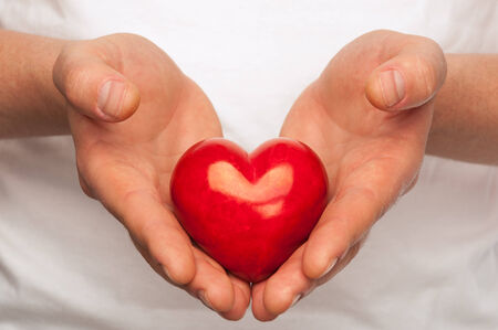 hands holding heart: Man with red heart in his hands over body background. Stock Photo