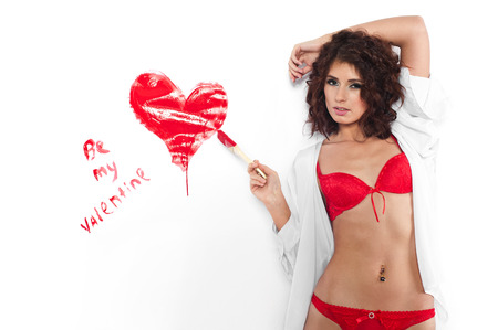 Young woman painting on the wall a red heart with paint brush in a be my valentine concept. Isolated on white. photo