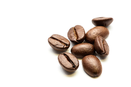 Close-up of roasted coffee beans heap isolated on white. Studio shot.