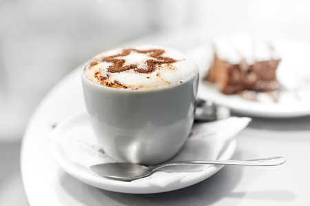 coffee froth: Cup of coffee and cake in cafe, shallow DOF, high key.