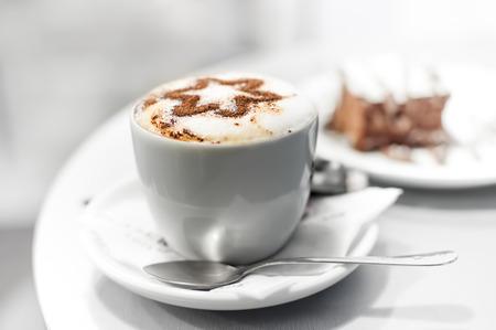 capuchinos: Taza de café y pastel en el café, DOF bajo, alto clave. Foto de archivo