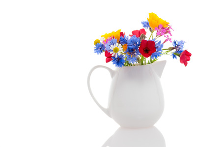 yellow wildflowers: Small white milk jug with wildflowers isolated on white background.