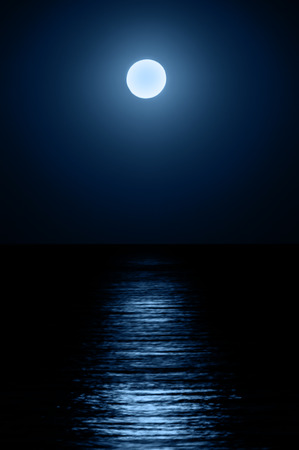 horizon over water: Reflection of the moon on the sea surface. Moonlight path.
