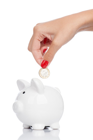 A womans manicured hand dropping a coin into a piggy bank isolated on white. Stock Photo