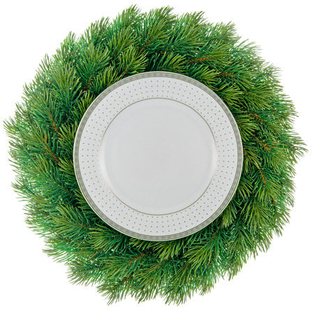 Plate in a christmas wreath isolated on white.