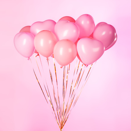 Bunch of pink party balloons on pink background.