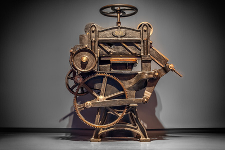 Antique printing press over grey background with vignette.