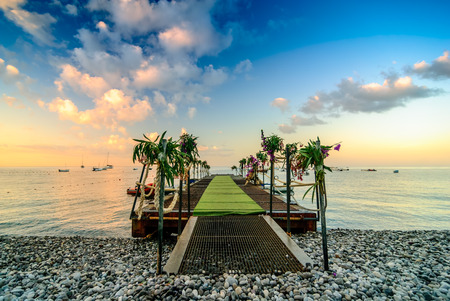 public holiday: Sunrise over the sea with pier on the foreground. The pier decorated with flowers for public holiday.