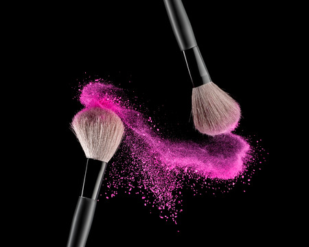 makeup: Make-up brush with pink powder explosion on black background