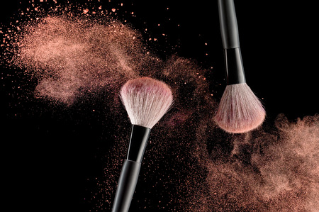 woman close up: Make-up brush with pink powder explosion on black background