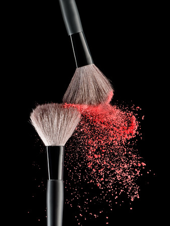 Make-up brush with pink powder explosion on black background