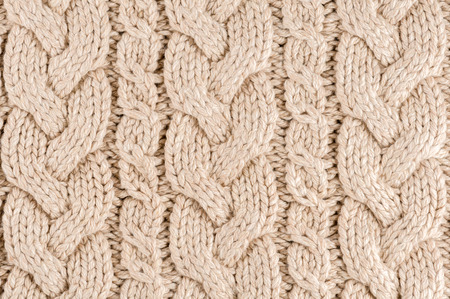 cable stitch: Knitted fabric texture close-up, beige color,  aran Sweater. Stock Photo