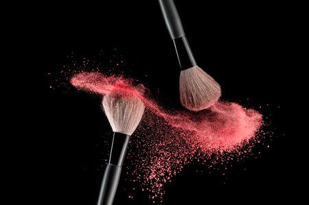 Make-up brush with pink powder explosion on black background