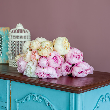 chest of drawers: Bouquet made of artifical pink peony laying on a commode. Shot against pink wall background. Shallow DOF. Stock Photo