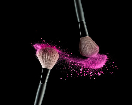 beauty make up: Make-up brush with pink powder explosion on black background