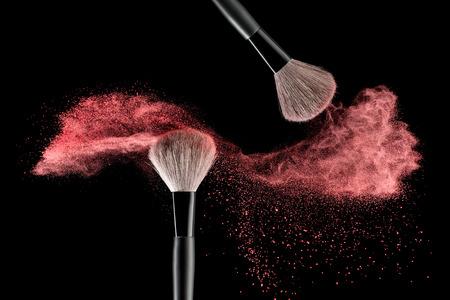 maquillage: Pinceau de maquillage avec du rose explosion de poudre sur fond noir