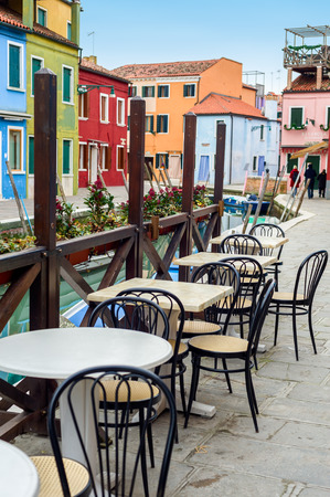 canal street: Street view of a cafe terrace with empty tables and chair on the famous island Burano, Venice, Italy.