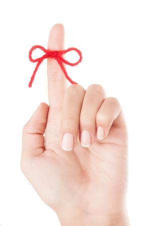 Rode strik op vinger geïsoleerd op een witte achtergrond.