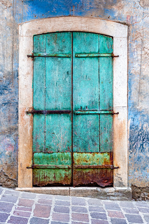 Turquoise grunge door. The photo taken in a small town in the middle of the Cilento and Vallo di Diano National Park  in Campania, Italy.