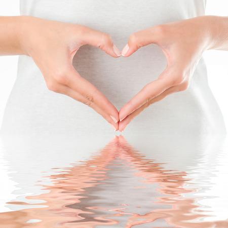 corazon humano: La forma de coraz�n por las manos femeninas en el fondo del cuerpo aislado en blanco.