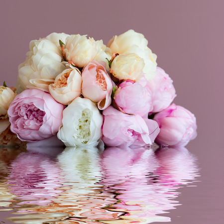 artifical: Bouquet made of artifical pink peony laying on a  watersurface. Shot against pink wall background. Shallow DOF.