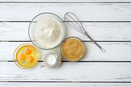 flour: Eggs, flour, milk, brown sugar with whisk on white wooden table from above.
