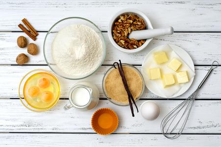 pastel: Hornear el pastel en la cocina rural - ingredientes de la receta (huevos, harina, leche, mantequilla, az�car, nueces, especias) en blanco mesa de madera desde arriba.
