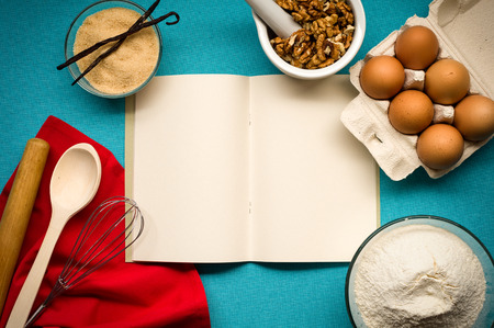Pure notebook for recording menu, recipe on blue tablecloth with red napkin, kitchen utensils and flour, vanilla, sugar, eggs, walnuts. Close- up view from top.