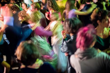 Dancing crowd at night, abstract motion blur photo.