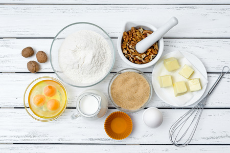 Baking cake in rural kitchen - dough recipe ingredients (eggs, flour, milk, butter, sugar) on white wooden table from above. Stock Photo