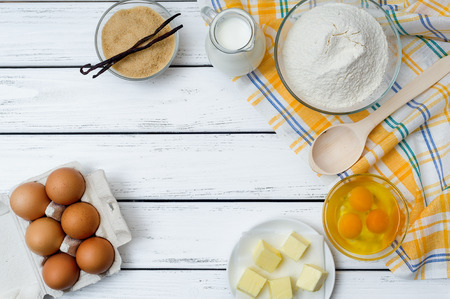 dough: Baking cake in rural kitchen - dough recipe ingredients (eggs, flour, milk, butter, sugar) on white wooden table from above. Stock Photo