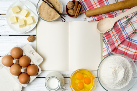 recipe book: Baking cake in rural kitchen - dough recipe ingredients (eggs, flour, milk, butter, sugar) with recipe book, wooden spoon, whisk, rolling pin and kitchen towel on white wooden table from above.