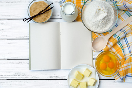 Baking cake in rural kitchen - dough recipe ingredients (eggs, flour, milk, butter, sugar) with recipe book, wooden spoon and kitchen towel on white wooden table from above. Zdjęcie Seryjne