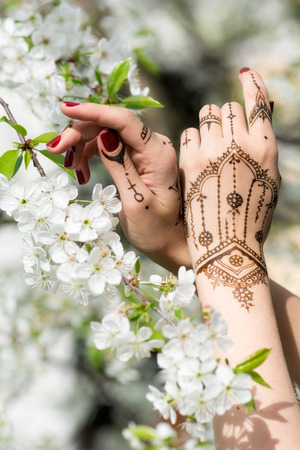 indian tattoo: Red manicured hands with Mehndi in spring cherry blossom, Indian tradition. Vertical composition.