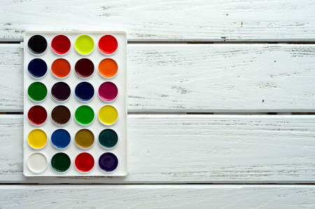 creative background: Desk of creative worker. Paints on wooden white background, top view, with copy space.