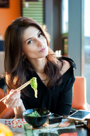 Young woman eating japanese seaweed salad Chuka in a sushi restaurant. Standard-Bild
