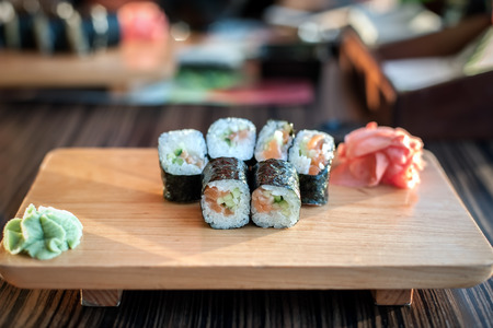 table set: Sushi rolls served on a wooden plate in a restaurant.