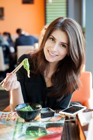 algas marinas: Mujer sonriente joven comiendo ensalada de algas japonés (Chuka) en un restaurante de sushi.