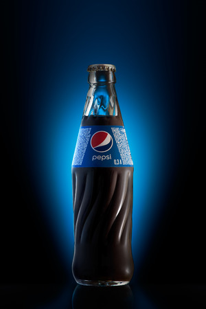 sodas: Kyiv, Ukraine - September 13, 2015: Photo of Pepsi glass bottle on black with blue background light. Pepsi is a carbonated soft drink that is produced and manufactured by PepsiCo.