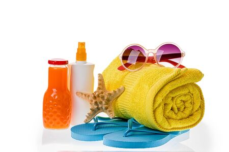 Bright beach accessories isolated on white: flip-flops, sunscreen, sunglasses, towel, starfish, juice. Zdjęcie Seryjne