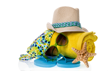Collection of beach items - towel, flip-flops, sunglasses, swimsuit and hat isolated on white.