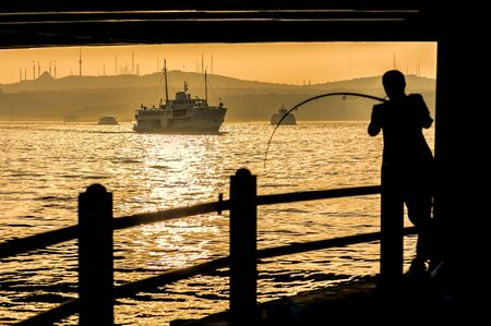 fishing catches: Fishermen silhouette under Galata bridge with ship on the Golden Horn, Istanbul, Turkey.